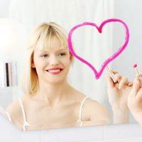 Young beautiful woman drawing big heart on mirror in bathroom.